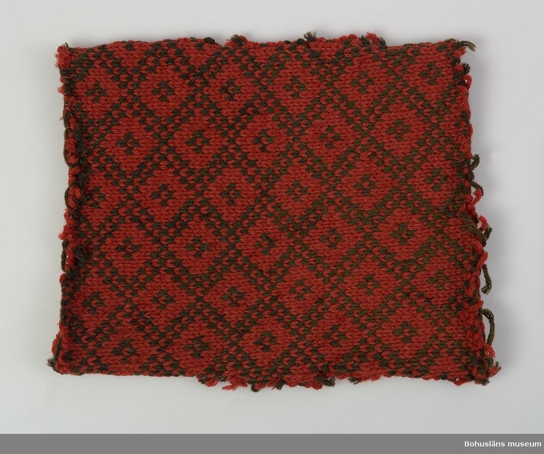 """Mönsterstickad bit, enligt tidigare katalogisering från en tröja. Heltäckande mönster bestående av diagonala rutor med små """"kors"""" i  mitten. Bottenfärg: Brunaktigt röd. Rombernas färg: Mycket mörkt brunt  (tidigare svart?). Mörka färgen blekt. Personuppgifter se UM016300."""