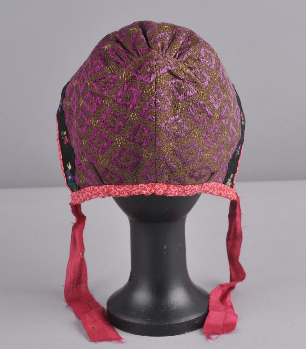 Luve av eit rektangulært stoffstykke, med saum i nakken og rynker på issen, i ull og silke. Brun botn med lilla og gul brosjering, kanting rundt luva av bomullslerret med trykt mønster i raudt og rosa. I framkant ei blomebore i svart, rosa, grønt, blått, gult og kvitt.  For av kvitt bomullslerret. Knytebanda er raude silkeband. Luva er handsauma.