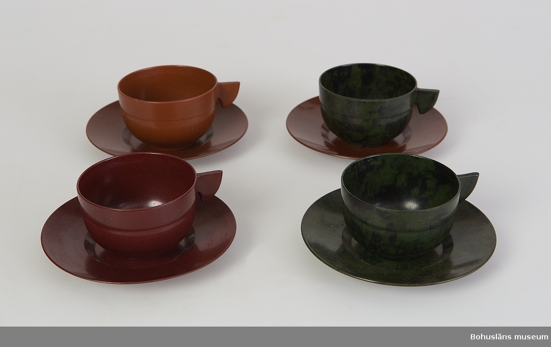 Fyra kaffekoppar med fat tillverkade av bakelit. Två bruna och två gröna koppar, tre bruna och ett grönt fat.