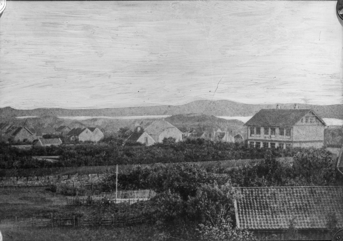 Middelskolen i Haugesund til høyre, med mange vinduer og to skorsteiner. Hustak og trær i forgrunnnen. Gjerde. Flere bolighus i bakgrunnen. Sjø og fjell lengst i bakgrunnen.