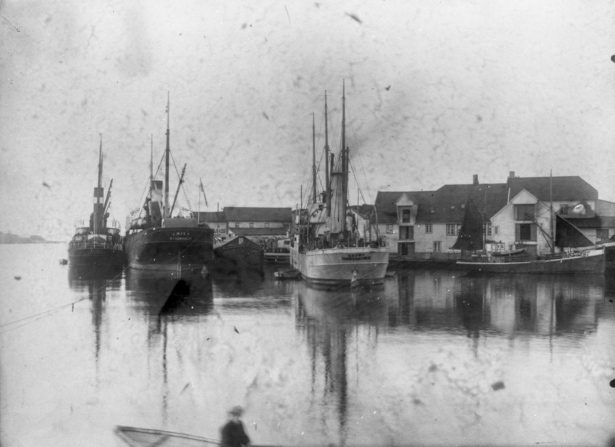"""Tre dampskip, bl. a. D/S """"Emily Stockholm"""", og en seilskute (til venstre) ankret opp ved Hansavåg. Sjøhus i bakgrunnen. Deler av en færing med en person ombord midt på bildet."""