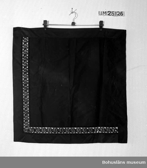 """503 Kön KVINNA Kvadratisk svart schalett av sidenrips, med påsydda kanter av samma tyg ytterst och en infälld maskintillverkad silkespets innanför kanterna längs två sidor. Spetsen fastsydd för hand. Kanterna längs de andra sidorna fastsydd med symaskin. Dateringen osäker, satt till 1900 ca för att markera att schaletten kan vara från slutet av 1800-talet. Troligare är dock början av 1900-talet. Något smutsig. Litteratur; Håkansson, Elin, Sidenhalsdukens bruk och tillverkning ur """"Sörmlandsbygden"""" 1933. Lewis, Katarina, Schartauansk Kvinnofromhet i tjugonde seklet, Uddevalla 1997, sid. 126. Lindvall-Nordin, Christina, Mossrosor och hjärtblomster ur Kulturens årsbok 1969, Lund. Wulfcrona-Dagel, Marie Louise, Schaletter och halskläden i Nordiska museet vävda hos K A Almgrens sidenväveri i Stockholm, uppsats för fortsättningskurs i etnologi, Stockholm 1979."""