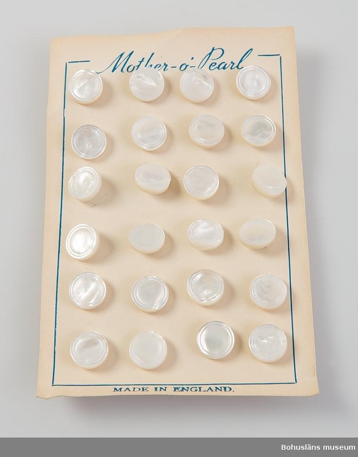 En uppsättningar med 30 fastsatta skjortknappar av vit pärlemo fastsatta mot kartongblad. På framsidan tryckt text: Mother - o -pearl samt MADE IN ENGLAND. Knapparna har en yttre dekorrand i relief. På baksidan ögla med rostfri klammer. Se UM031726.