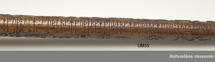 Käpp tillverkad av en runstav, kompletterad med krycka av elfenben samt doppsko av mässing. Skador på kryckan; sprickor samt del av handtaget bortslaget. Runstaven är troligen tillverkad av björk, skurna figurer i högrelief, runor skurna i lågrelief; arbetet svärtat och polerat. Runstaven daterad till 1600-talet.  Tullkontrollör A. Kidron var sedermera tullförvaltare i Kalmar. [Uppgiften väcker frågor - undrar om inte tullkontrollör Kidron har fått fel begynnelsebokstav på förnamnet? I Sveriges statskalender/1881 finns en Kidron antecknad i Kalmar: Tullförvaltare, Carl Erik Reinhold Kidron, R. W. O., f. 26; 79; utöfvar jemväl chefskap öfver kustbevakn. i Kalmar tullkammar distr.  /Marie Johansson i oktober 2012]  Se artikel av Sten kristiansson i klipp-pärmen Glimtar från Uddevalla museum med artiklar om Uddevalla museum publicerade i Bohus-Posten åren 1940-1942; Runstavar. Bohusläns museums bibliotek, NcbkzN-Uddevalla  I 1869 års tryckta katalog G N:o 20: En runstaf med elfenbernskrycka och upphöjda figurer.  Ur Nationalencyklopedin, NE.se: Runkalender Runkalender, en form av evighetskalender (jfr kalender), där beteckningarna för veckodagarna och gyllentalen utgörs av runor: futharkens sju första runor (upprepade 52 gånger) resp. futharkens 16 runor utökade med tre nyskapade tecken (placerade vid de datum då nymåne beräknas inträffa under vederbörande år i den 19-åriga måncykeln). Även de kyrkliga festdagarna kan vara angivna med runor. Runkalendrar har förekommit i olika utföranden, bl.a. skrivna på pergament eller ristade på trä, ben eller horn. Runkalendern tycks vara en medeltida svensk uppfinning, medan träkalendrar utan runor, men med dagarna markerade med streck eller hack i stavens kant, är kända från flera områden i Europa. Den äldsta bevarade runkalendern, ristad på en trästav, har daterats till 1200-talet (Nyköpingsstaven). Det tusental kalendrar av trä som är kända tillhör företrädesvis 1500- och 1600-talen. Under 1700-talet fick runkalendrar en renäss