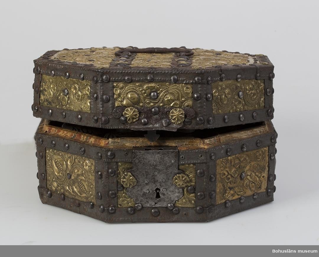 """Ett åttkantigt skrin för nio glasflaskor. Skrinet är ett holländskt arbete från 1600-talet. Skrinets utsida är beslagen med mässingsplåt, ca 0,2 mm tjock och hålls på plats med smidda band och prydnadsband av järn. Mellan banden framträder dekorativa rektangulära mässingsfält. Lockets två parallella band är klippta i ett löpande åttakantigt mönster passande skrinets form. Mässingsplåten är rikt dekorerad med blommor, hjärtan, cirklar och löpande linjer vilka formats med puns eller pressats fram. Invändigt är skrinet rödbemålad i dess undre del med vad som troligen är tunn oljefärg, alternativt limfärg. Skrinets lock och den övre hälften av skrinets underdel är klistrat med papper av två slag. Locket pryds av ett kopparstick av amoröst slag som utgör en mindre del av en större bild. Texten """"Tactus das fuhler"""", troligen motivets titel, är urklippt och placerad i anslutning till motivet. Ytterligare text beskriver kärlekens nöjen. Under titeln står """"zu finden bey Joh. Peter Wolff in Nurnberg"""". Övriga partier av ett marmorerat papper av holländskt slag. Marmoreringen är utförd med kam i rött, blått, vitt och gult.  Lock och underrede hålls samman av två smidda gångjärn. I uppfällt läge har locket hållits på plats med två rosafärgade linneband. Skrinets lås har låsbricka av järn dekorerat med ciselerade bladslingor. Skrinet har kunnat bäras i ett handtag av smidesjärn, fästat ovanpå skrinets lock. Inuti skrinet står sju mindre flaskor av blåst glas, (höjd 11 cm, diameter 7 cm) samt en större flaska (höjd 13 cm, diameter 10 cm). Flaskorna har svarvade och stämplade skruvlock av tenn. Flaskornas skuldror är dekorerade med bladguld lagt i olja och föreställer blad, blommor och torligen frukter. Utförande är ganska grovt med obehandlade geringar, och sammanfogning med mindre spik. Om Johann Peter Wolff finns uppgifter att han gjorde kopparstick på 1700-talets början. Ur handskrivna katalogen 1957-1958: 8-kantigt skrin med 8 glasflaskor [en flaska saknas av de nio platser för"""