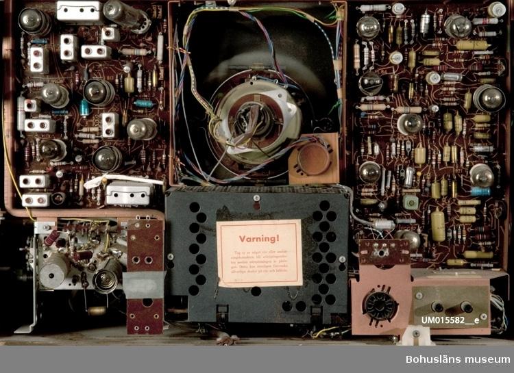 21-tums TV inbyggd i teakskåp med skjutdörrar dvs. dubbla jalusiedörrar som dras för rutan från sidorna när apparaten inte används. Sladd med stickkontakt avklippt. Apparaten var utställd i gamla basutställningen, 1960-talet.
