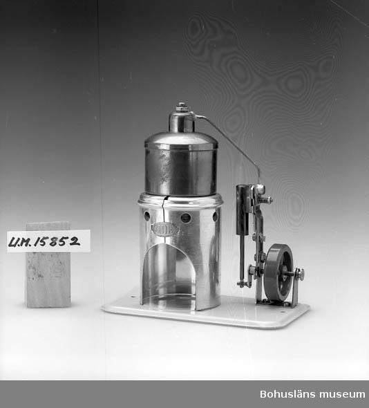 Består av tryckbehållare, kolv och hjul, behållare för fotogen saknas. Förvaras i kartong utan tryck och text.  Se UM15810.