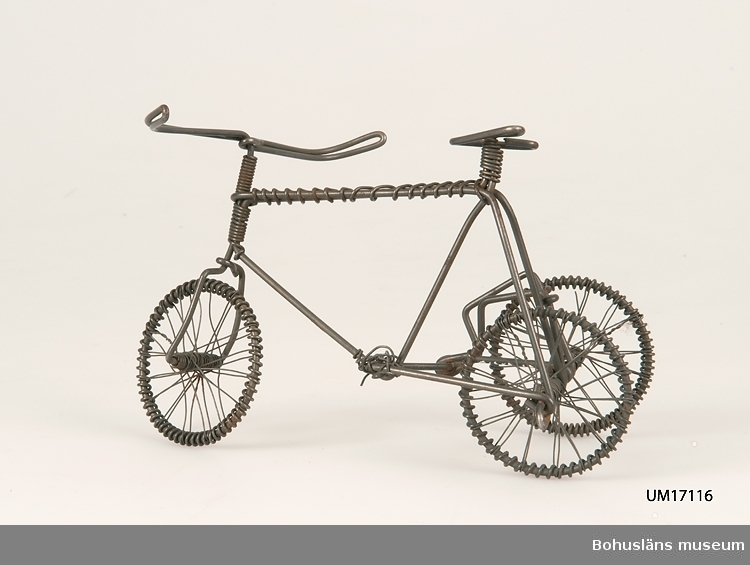 503 Kön MAN  Tillverkad av göteborgare av järntråd. Han fabricerade leksaker och miniatyr föremål som han sedan gick omkring och saluförde. Tidningsartikel om tillverkaren var införd i Handelstidningen eller GP omkring 1970.