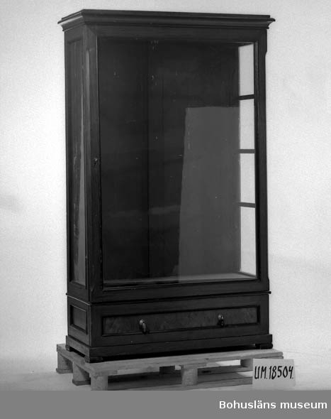 471 Tillverkningstid C:A 1900 410 Mått/Vikt !L.176  B.107 DJ.46 10 Vitrinskåp i ekfanerad furu. Gavlar och front med glas.Underst en 20 draglåda.Dekorativa lister i svärtat trä. Tillhörde det gamla 30 mönstersystemet på Uddevalla museum, Kungsgatan 30.