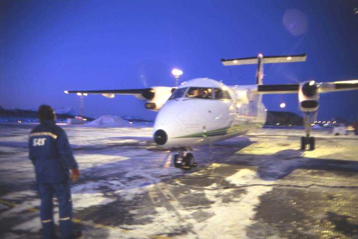 Lufthavn/Flyplass. Bodø. Et fly, DHC-8 /Dash8 fra Widerøe starter opp. Marshall fra SAS hjelper til med oppstart.