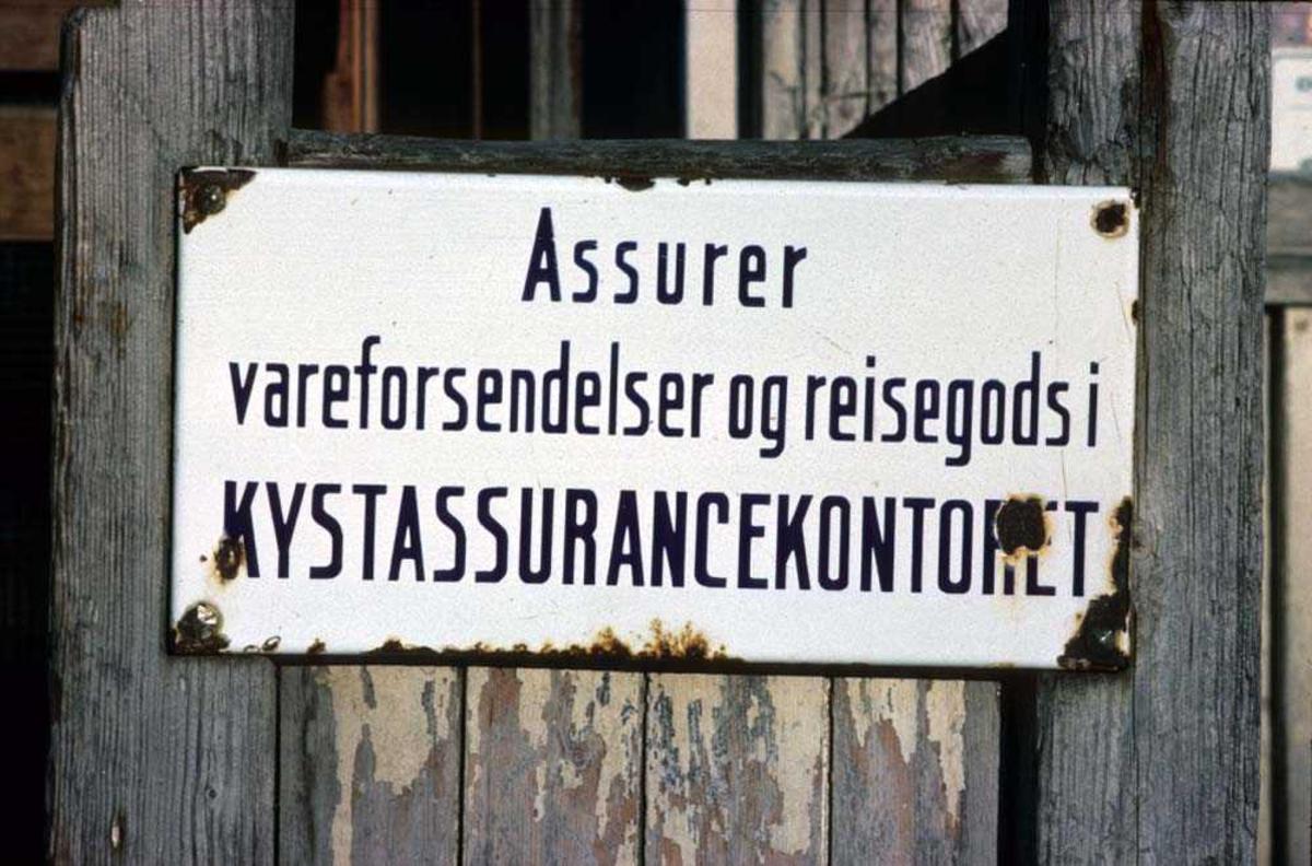 Landskap. Gammelt originalt skilt viser hvor en kan forsikre sine eiendeler. Ett sted i Vesterålen.