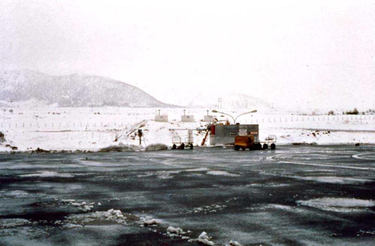 Lufthavn/flyplass. Stokmarknes/Skagen. Motiv hentet fra en snøryddet tarmac med tankanlegget i bakgrunn.