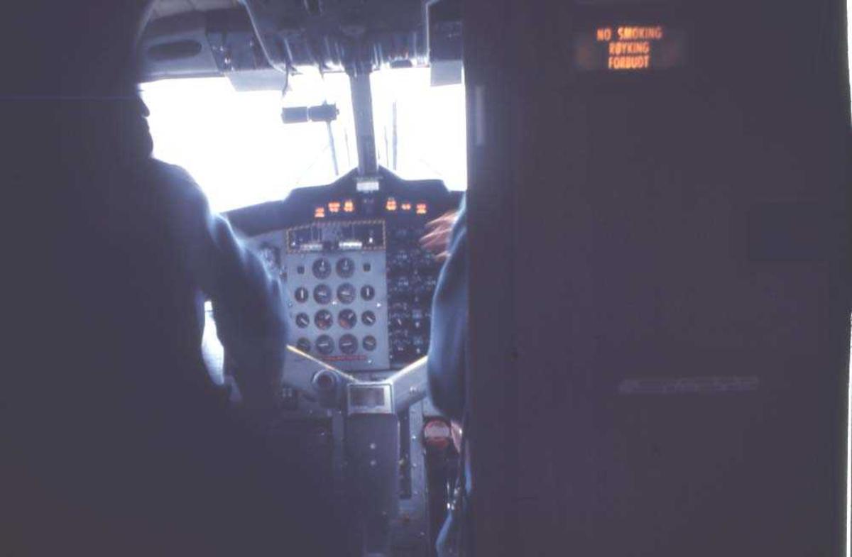 Lufthavn/flyplass. Florø. Parti av instrumentpanelet til et fly, DHC-6-300 Twin Otter fra Widerøe. 2 piloter/flygere skimtes gjennom cockpitdøra.