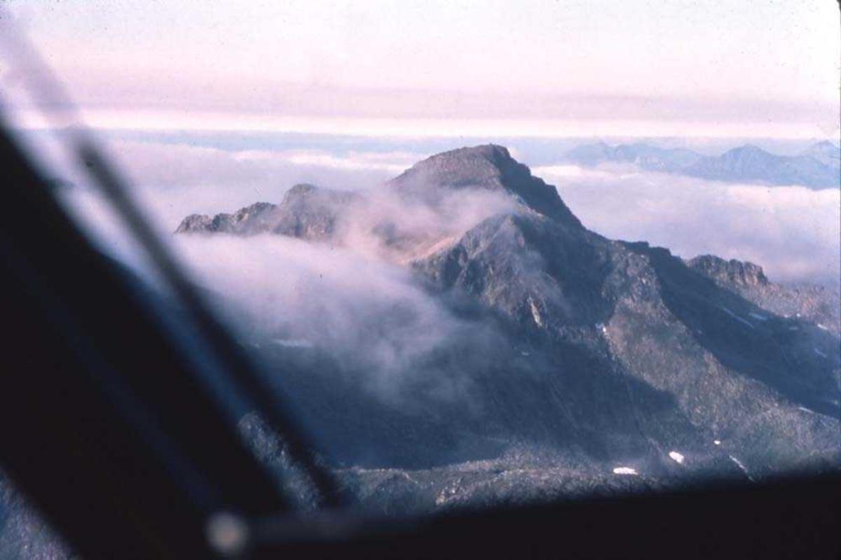 Luftfoto. Et fly, DHC-6-300 Twin Otter fra Widerøe passerer majestetiske fjellformasjoner mellom Tromsø og Hammerfest.