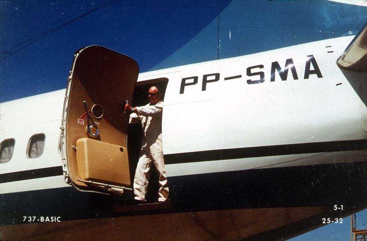 En person som åpner/lukker bakre dør på ett fly, Boeing 737-200 PP-SMA.