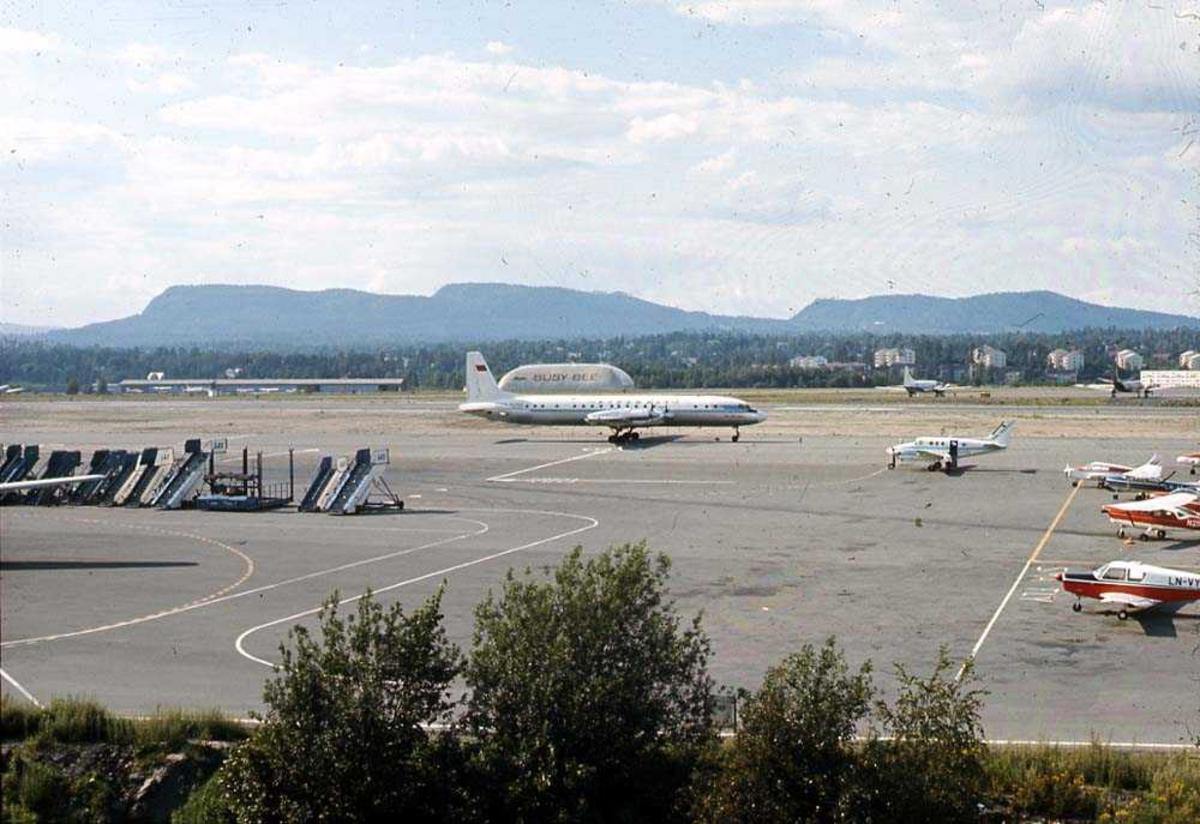 Lufthavn. Ett fly på bakken, Illyushin Il-18D Coot CCCP-74258 fra Aeroflot. Flere andre fly til høyre i bildet. Bygninger og fjell i bakgrunnen.