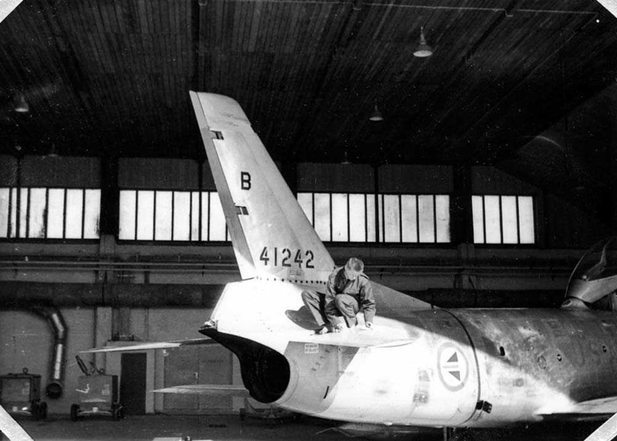 Ett fly inne i en hangar. En person som sitter bak på flyet.