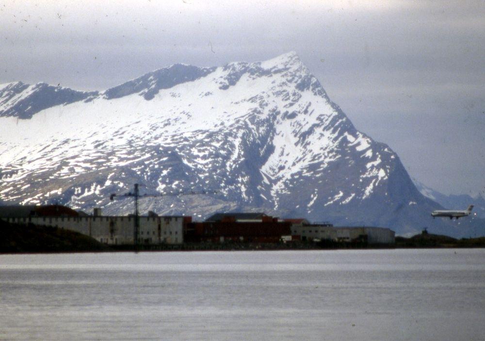 Landskap. Et fly, Douglas DC-9 fra SAS under innflyging til Bodø bane 08. I bakgrunn fjellet Sandhornet (Sandhornøya/Gildeskål) sør for Bodø.