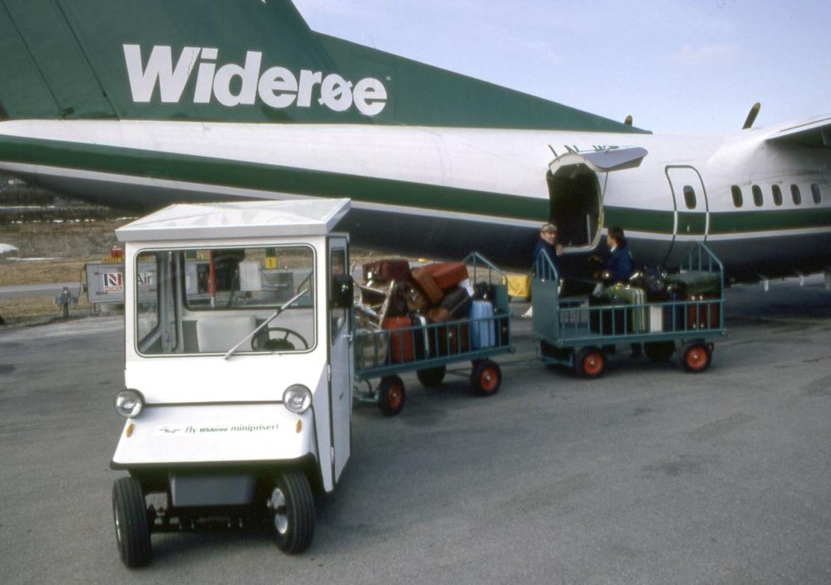Lufthavn (flyplass). Et fly, DHC-7-102 Dash 7 fra Widerøe parkert. To personer laster/losser flyet.
