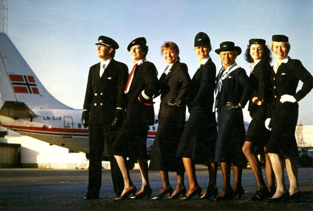 Portrett. Kabinansatte i Braathens SAFE poserer i selskapets forskjellige uniformer opp gjennom tiden, ved siden av et fly, LN-SUB, Boeing 737.