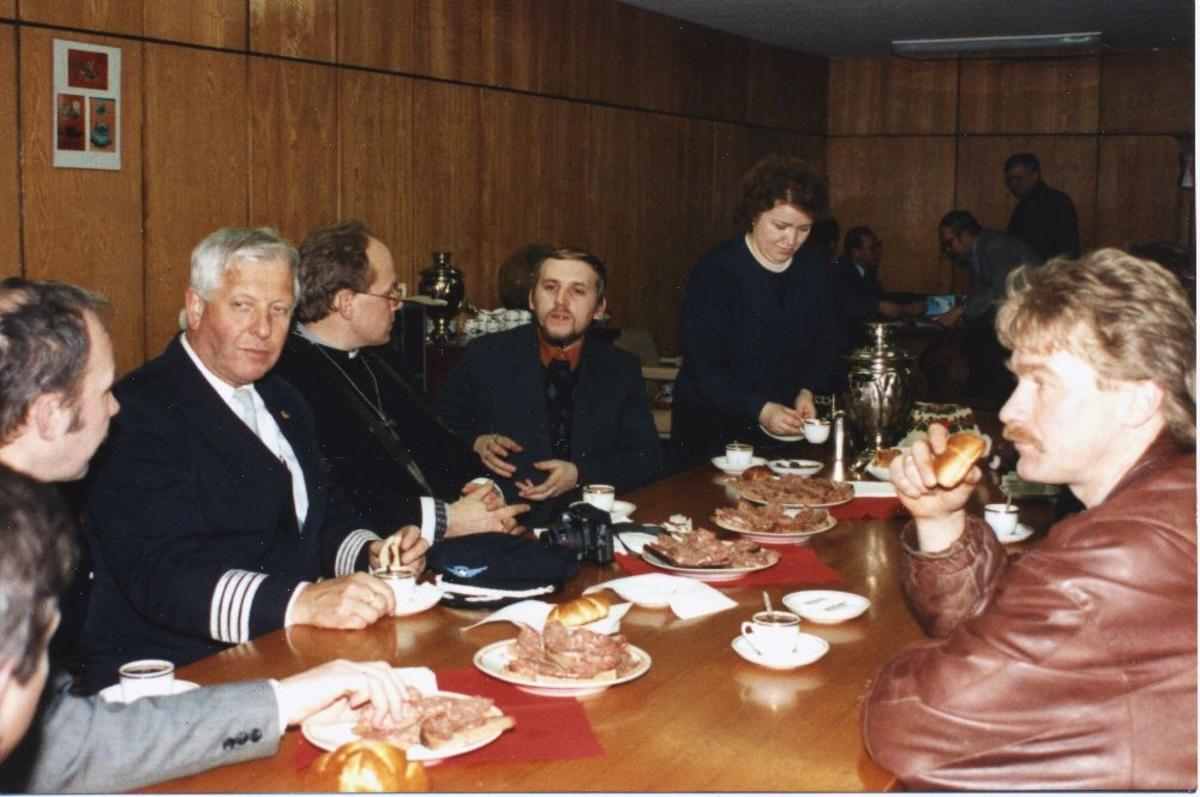 Landskap. Murmansk. Braathens SAFE,s første flyvning. En gruppe personer deltar i felles måltid. Flykaptein fra Braathens SAFE er også med.