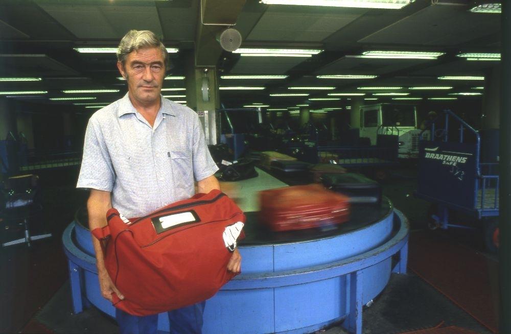 Lufthavn/flyplass. En person/stuer fra Braathens SAFE håndterer bagasje ved transportbåndet.