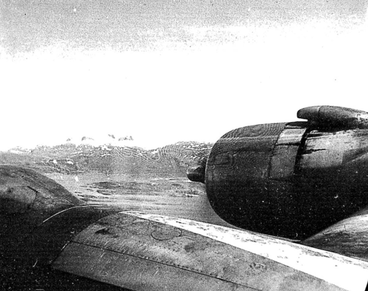 Luftfoto, tatt fra 1 fly, litt av vingen og motoren sees. Land og hav under.