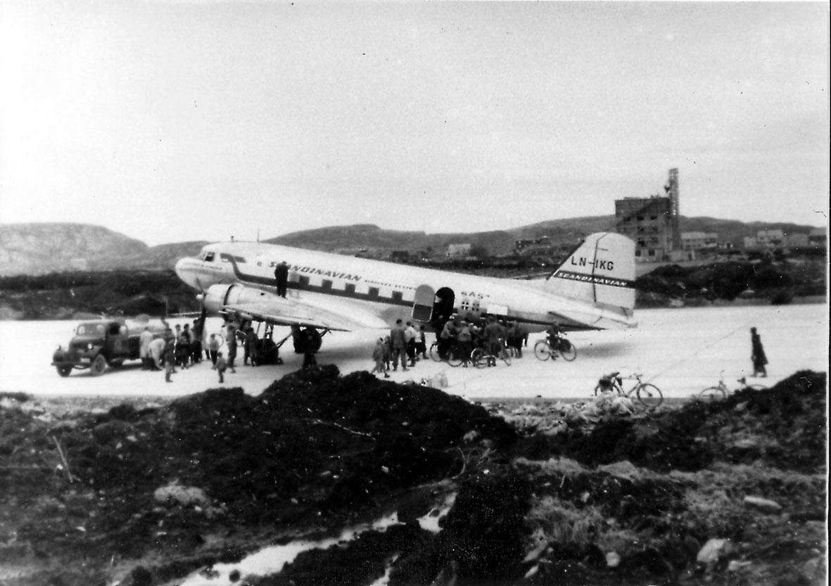 Lufthavn, 1 fly på bakken, C-47A-15-DK, LN-IKG fra SAS. Flere personer, noen av dem på sykler, og et kjøretøy, ved flyet. Kontrolltårnet under bygging i bakgrunnen.