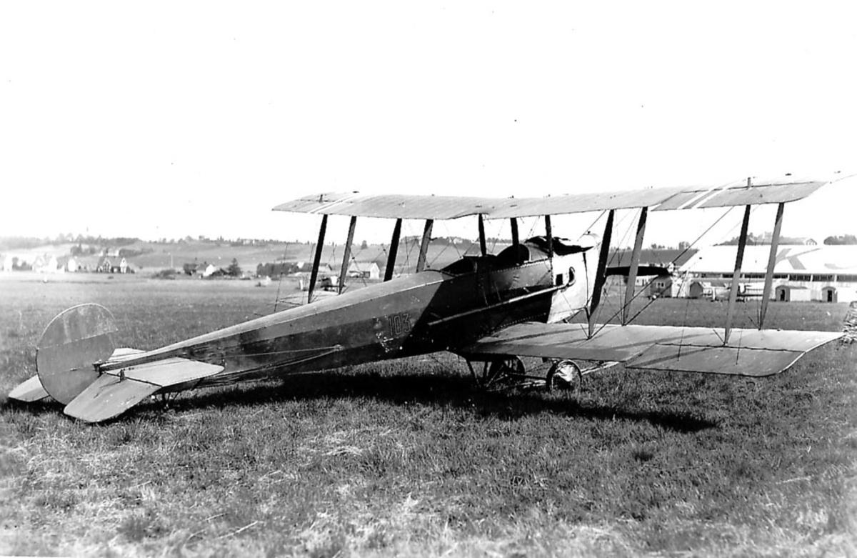 Lufthavn. Ett fly på bakken, Avro 504, Nr. 103. to andre fly og flere bygninger i bakgrunnen.  Kjeller.