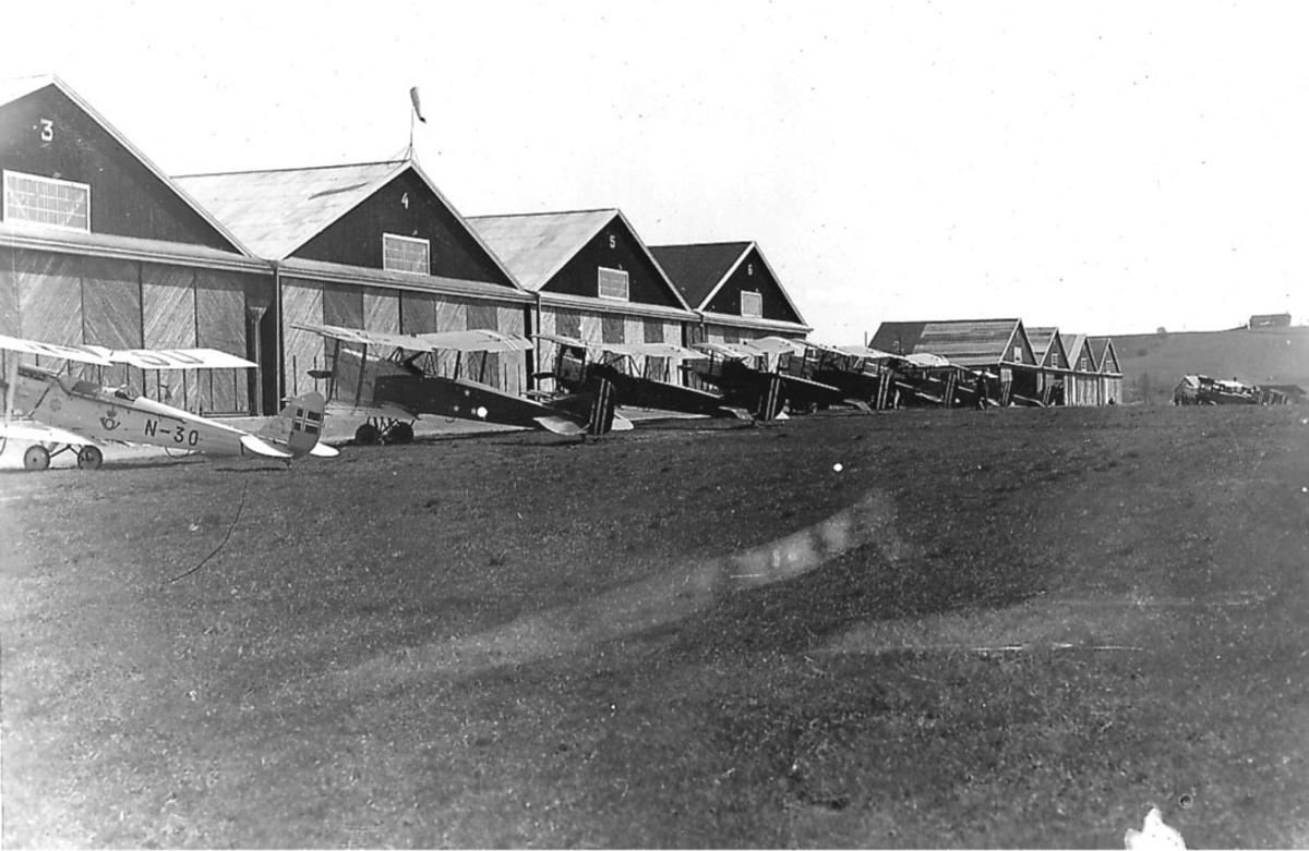 Kjeller, lufthavn. Flere fly på rekke, fem stk Kaje treningsfly, en sivil  DH 60M Moth  Reg nr N-30 foran. Flere bygninger bak flyene.