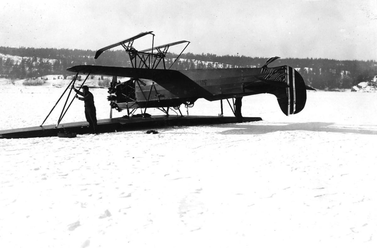"""Åpen plass, to personer ved ett fly som ligger på bakken, Fokker CVE nr 311, med skiunderstell. Snø på bakken. Flyet ligger på """"rygg""""."""