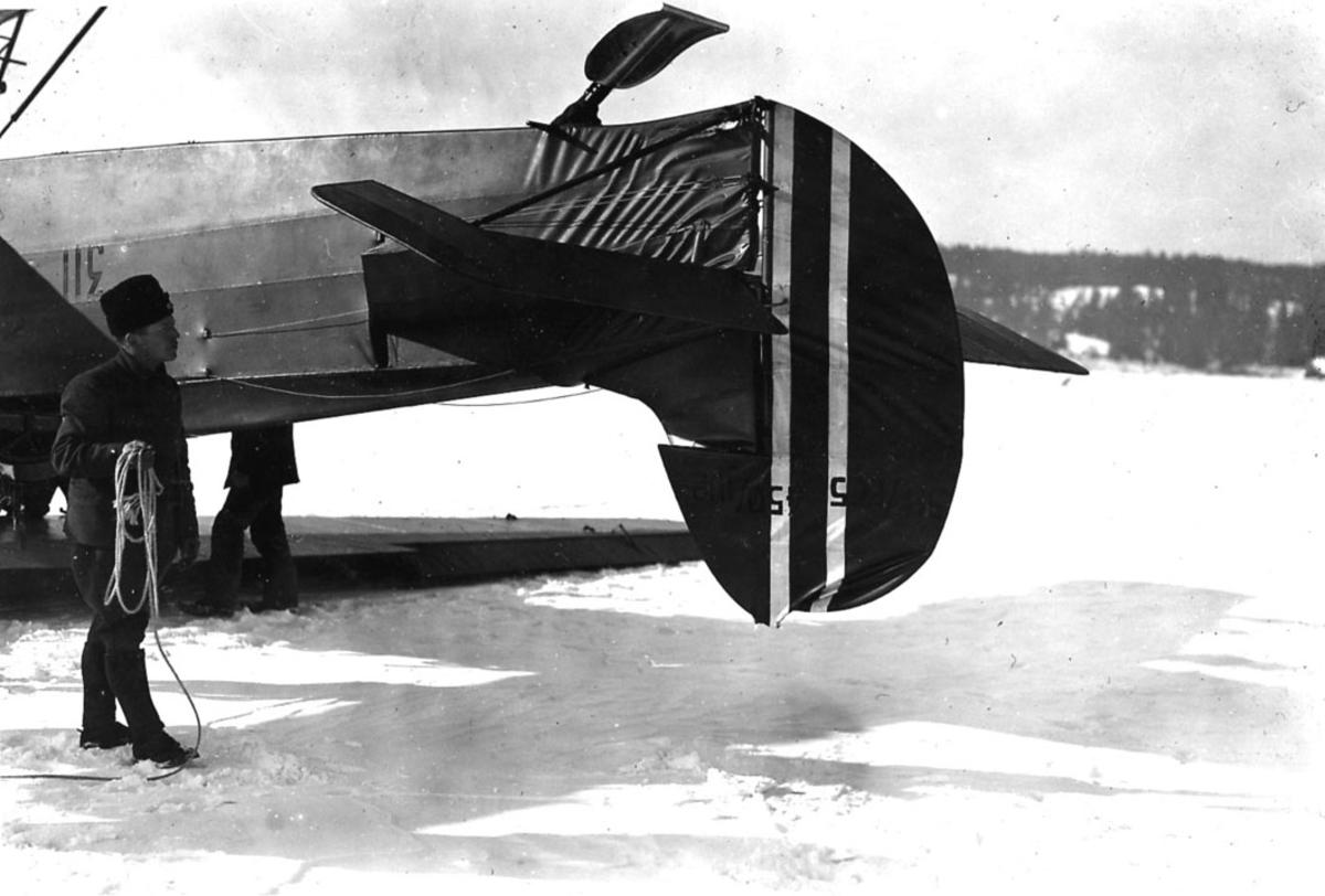 """Åpen plass, halepartiet til ett fly som ligger på bakken, Fokker CVE nr 311. Flyet ligger på """"rygg"""". to personer ved flyet."""