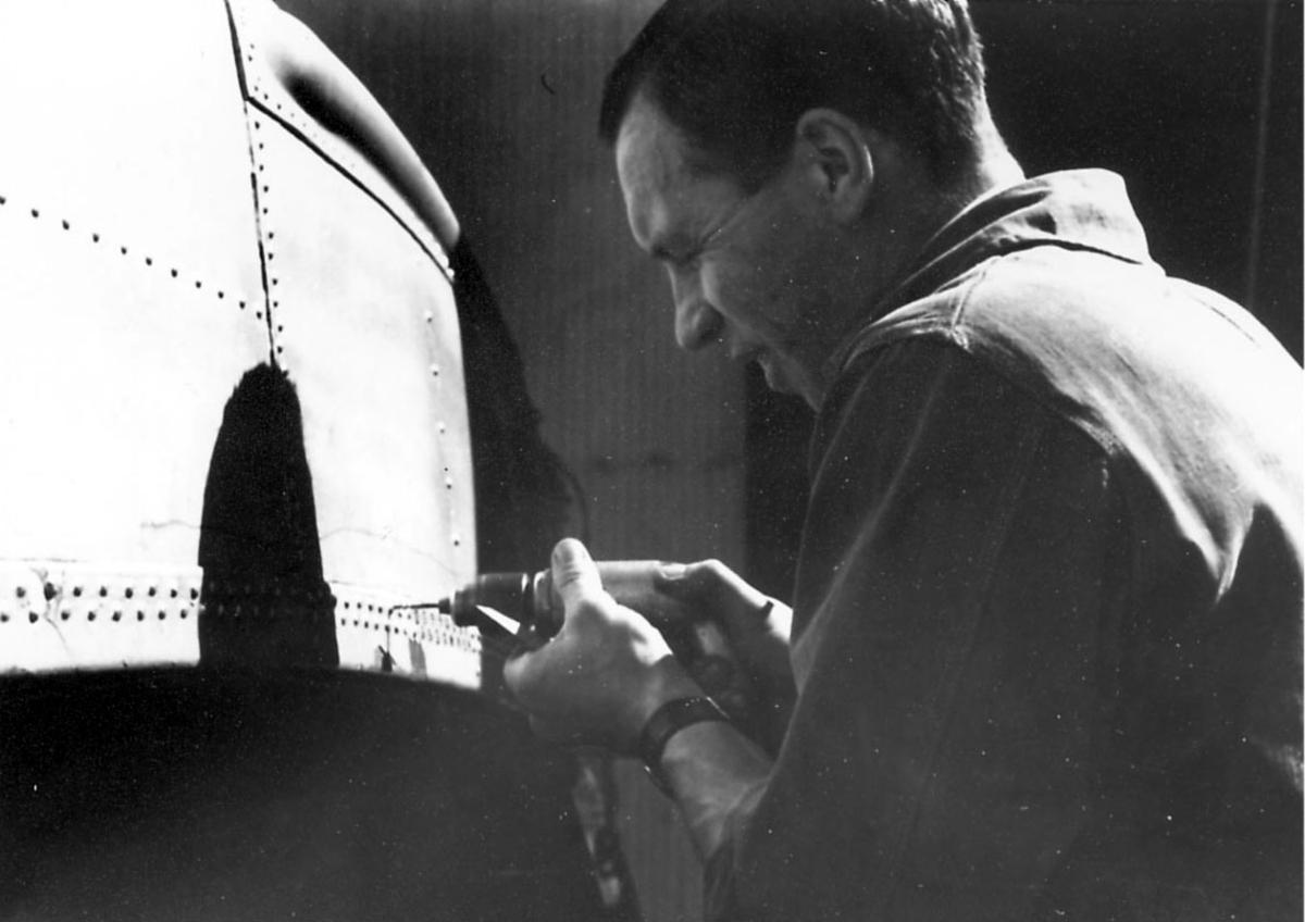 En person, verkstedarbeider/mekaniker i arbeid, ant. på ett flyskrog. Fester skruer med en skruemaskin.