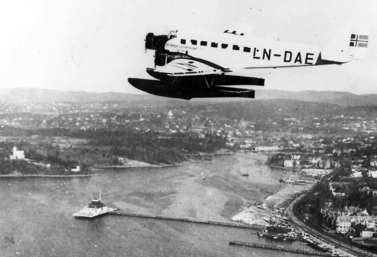 """Luftfoto, ett fly Junkers Ju 52/3mge LN-DAE """"Havørn"""". Bebyggelse, tettsted under."""