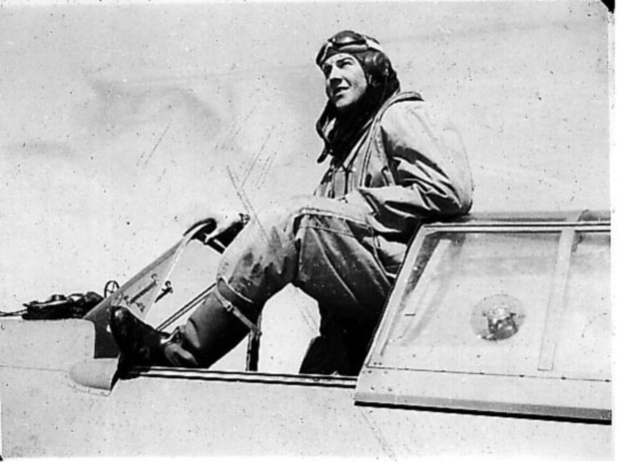 Portrett, en person, flyger, lener seg ut av cockpiten på et fly.
