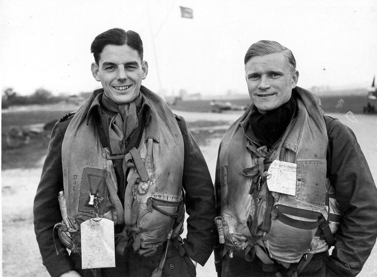 """Portrett, to personer,  flygere i """"full"""" utrustning, i flyuniform."""