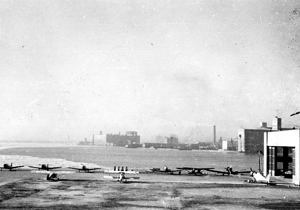 Ant lufthavn nede ved havneområdet. Flere fly oppstilt. Bygninger bak.
