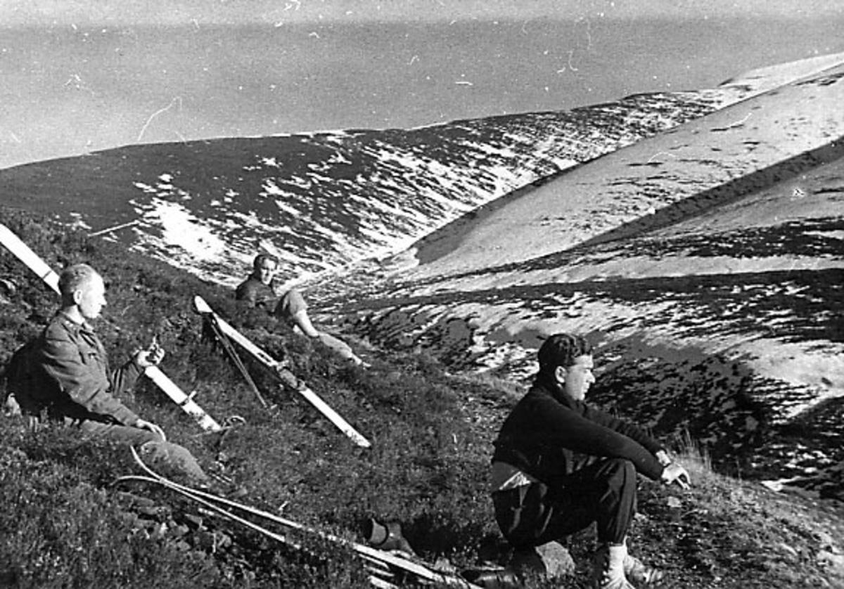 Portrett, tre personer sitter i fjellskråning. Skiutstyr ligger på bakken ved siden av.