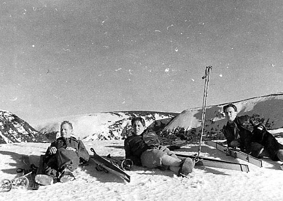 Portrett, tre personer ligger i ei fjellskråning. Skiutstyr ligger på bakken ved siden av. Snø.