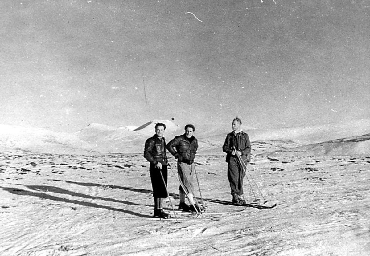 Portrett, tre personer på ski. Flatt snødekt fjellandskap.