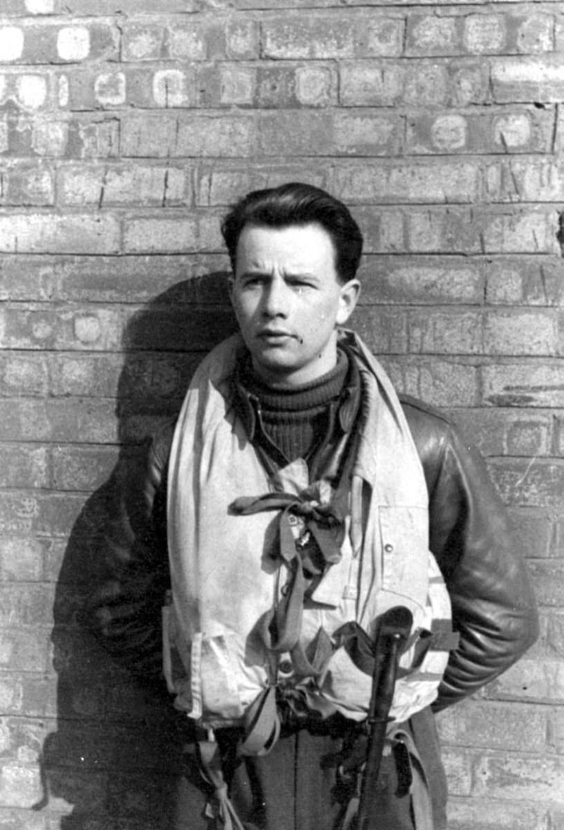 Portrett, en person, militær, i militæruniform, pilot lent mot en murvegg.