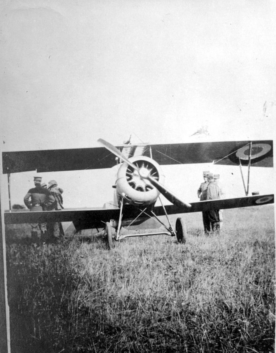 Fly, på bakken, Nieuport 17C.1. Sett forfra. Noen personer i militæruniformer ved flyet.