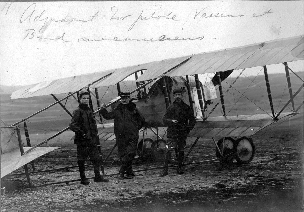 Fly, Caudron G-3. Skrått bakfra. Står på bakken. 3 personer foran.
