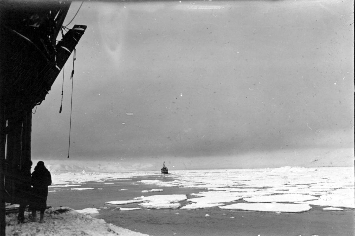 Fra kai (heiseutstyr?). 2 personer. Fartøy/båt utpå havet, i bakgrunnen. Hav, små isflak. Snø.