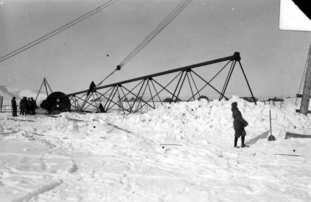 """Fortøyningsmasten til luftskipet """"Norge"""" ligger på bakken. Noen personer. Tau e.l. er festet til masten. Like før masten skal reises."""