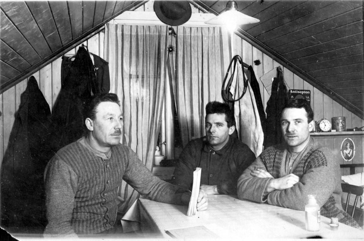 Portrett, tatt innendørs. 3 personer rundt et bord. Vindu, noen klær, hylle med div. gjenstander på veggen bak.