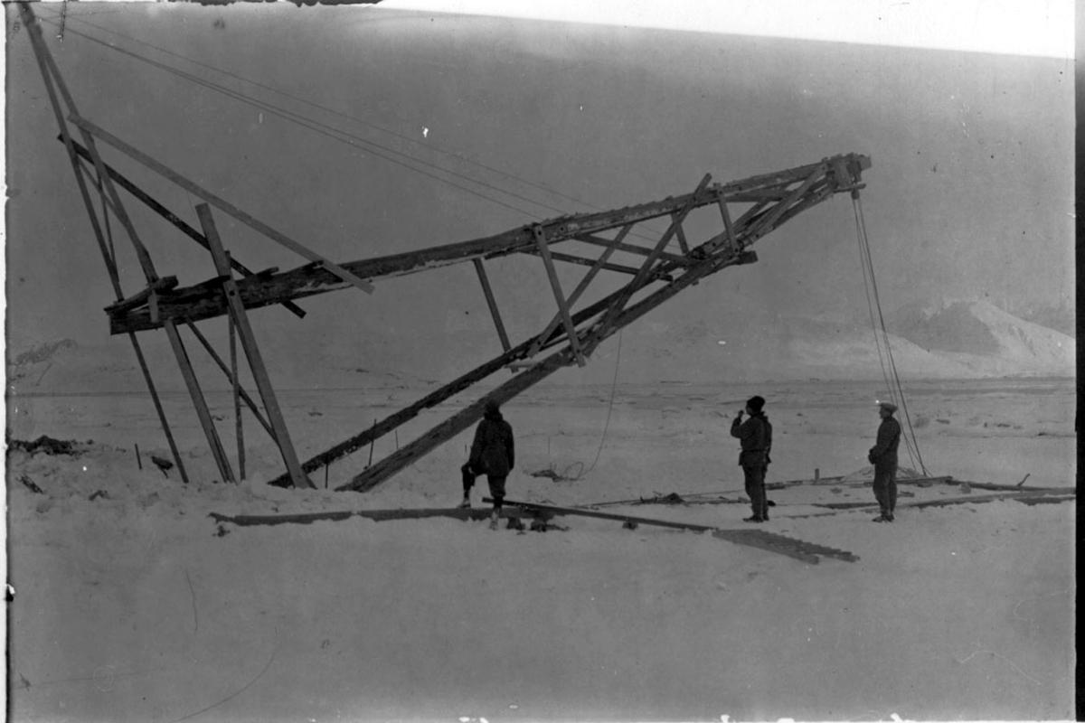 """Hjelpebukk for heving av fortøyningsmasten til luftskipet """"Norge"""", reises. Noen personer i arbeid. Snø på bakken."""