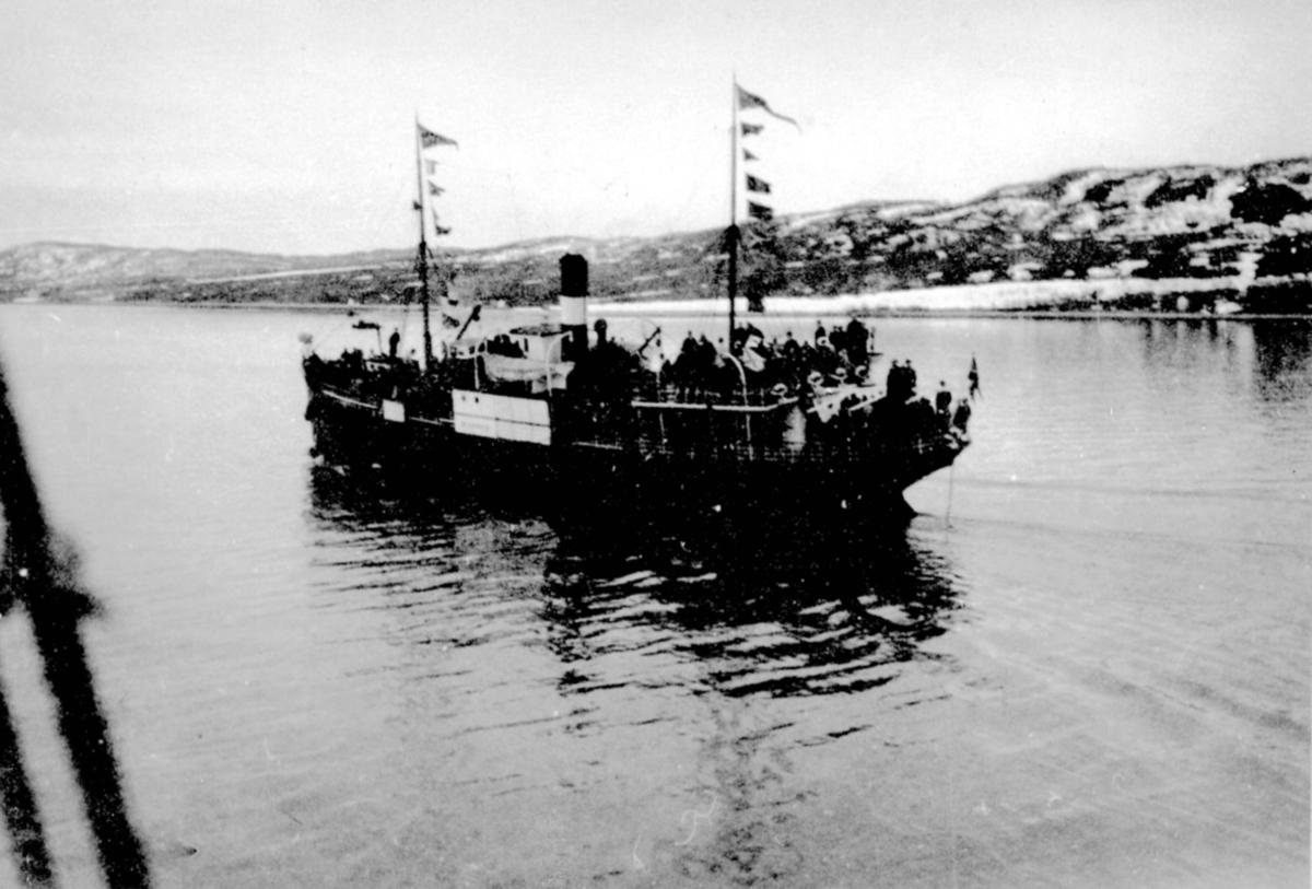 Fartøy i sakte fart ut en fjord. Mange personer på dekk. Vimpler/signalflagg i masteriggen.