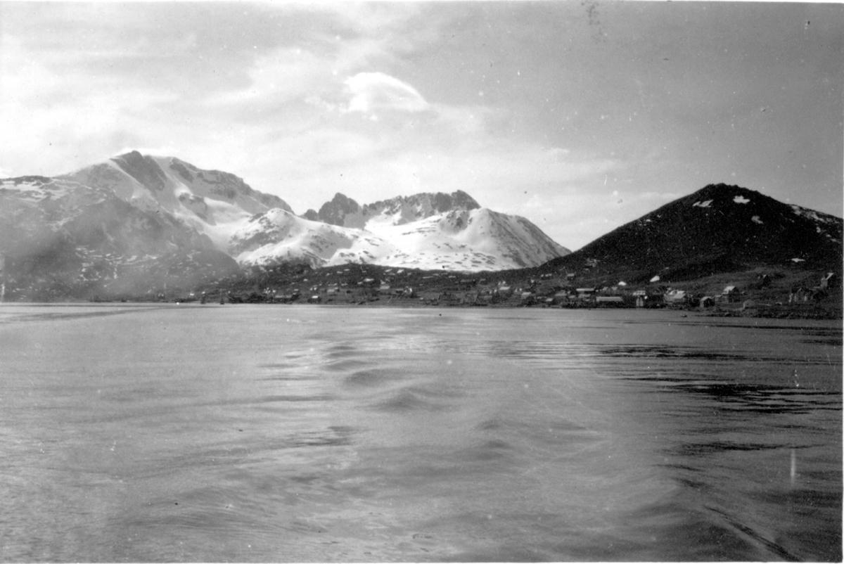 Havet, fjorden i forgrunnen. Bygninger - bebyggelse inne på land. Fjell i bakgrunnen