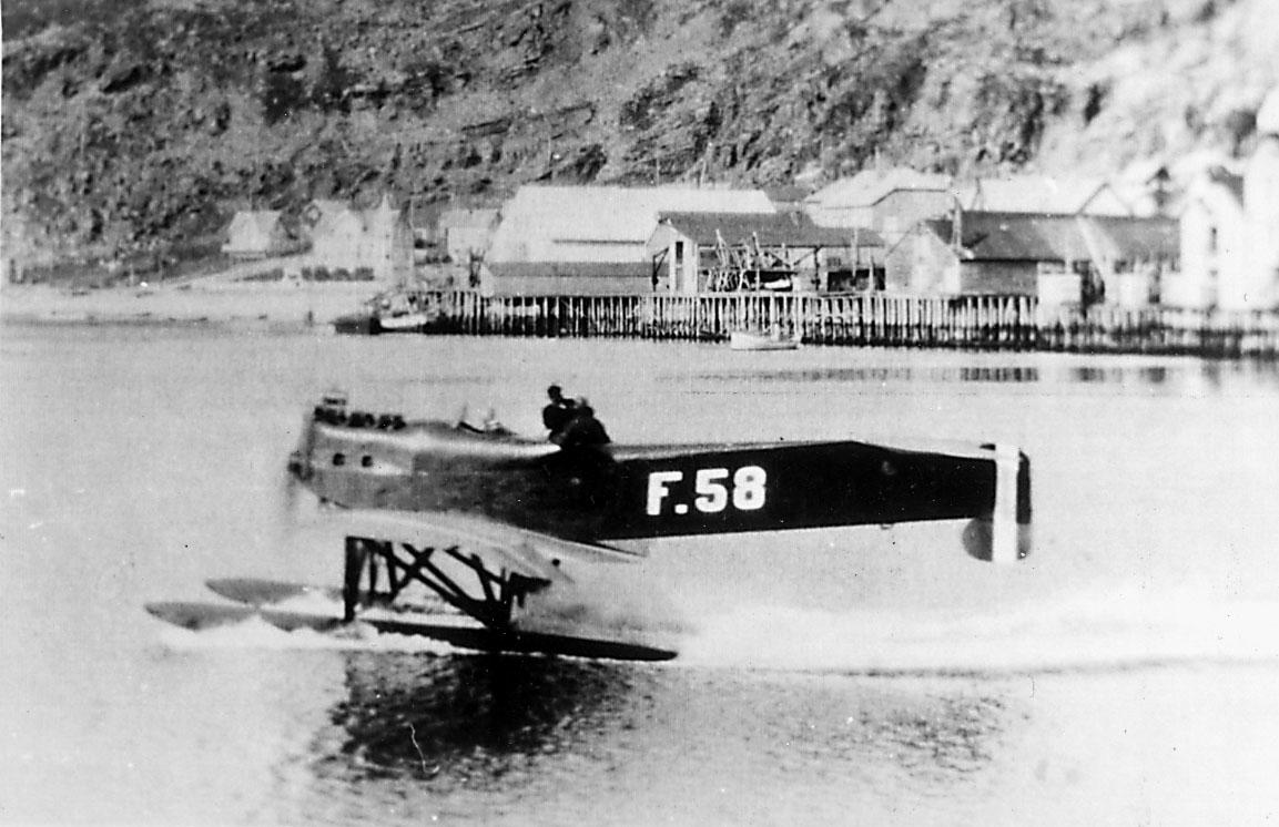 1 fly med 2 personer ombord i sakte fart på havoverflata. Hansa-Brandenburger Monoplan Tractor W.33 SFR.2, F.58 fra Marinens Flyvåpen.  Flere båter og bygninger i bakgrunnen.
